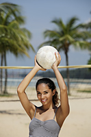 Young woman holding volleyball and smiling at beach - Asia Images Group