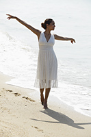 young woman with arms out stretched walking along the beach - Asia Images Group