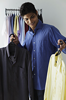young man looking at two shirts - Asia Images Group