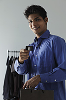 young man paying with credit card in shop - Asia Images Group