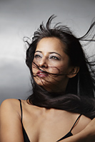 head shot of woman with hair blowing around her face - Asia Images Group