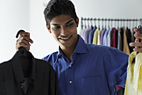 young man deciding between two shirts - Asia Images Group