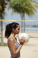 profile of young woman holding volleyball at beach - Asia Images Group