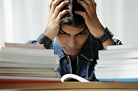 young man holding his head while reading - Asia Images Group