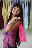smiling woman holding pink shopping bag over her shoulder - Asia Images Group