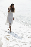 young woman wearing a white dress walking along the beach - Asia Images Group