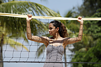 young woman holding onto volleyball net at beach - Asia Images Group