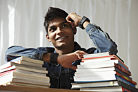 young man with a stack of books smiling and thinking - Asia Images Group