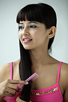 woman combing hair with pink comb - Asia Images Group