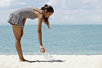 young woman picking up rubbish on the beach - Asia Images Group