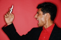 Man looking at handphone, mouth open, shouting - Asia Images Group