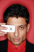 Man looking through camera phone, headshot - Asia Images Group