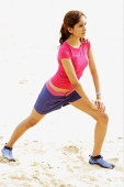 Young woman at the beach, stretching - Asia Images Group