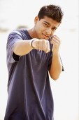 Young man throwing a punch, looking at camera - Asia Images Group