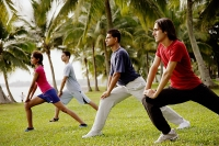 Young adults doing exercises in park. - Asia Images Group