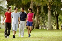 Young adults walking in park, side by side - Asia Images Group