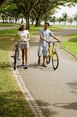 Couple wheeling bicycles in park - Asia Images Group