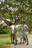 Couple standing with bicycles in park - Asia Images Group