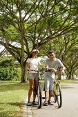 Couple standing with bicycles in park, looking at camera - Asia Images Group