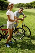 Couple on bicycles, looking at camera - Asia Images Group