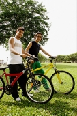 Two young men on bicycles, looking at camera - Asia Images Group
