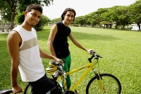 Two young men on bicycles in park, smiling at camera - Asia Images Group