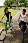 Two young men cycling side by side in park - Asia Images Group