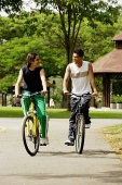 Friends cycling side by side in park - Asia Images Group
