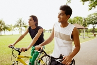 Two young men on bicycles, looking away - Asia Images Group