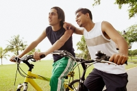 Two young men on bicycles, one leaning on the other, pointing - Asia Images Group