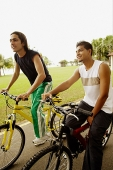 Two young men sitting on bicycles, looking away - Asia Images Group
