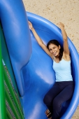 Woman sliding on slide, looking up at camera - Asia Images Group