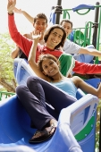 Three guys and a girl on slide, looking up at camera - Asia Images Group