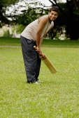 Man holding cricket bat - Asia Images Group