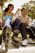 Man and woman lacing up roller blades - Asia Images Group