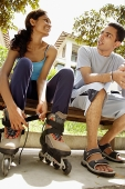Man and woman sitting on bench, woman lacing up roller blades - Asia Images Group
