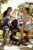 Man and woman on bench side by side, woman lacing up roller blades - Asia Images Group