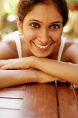 Woman resting head on arms, smiling at camera - Asia Images Group