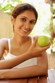 Woman holding apple, smiling - Asia Images Group