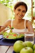Woman eating salad, looking at camera - Asia Images Group
