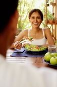 Woman eating salad, looking at man across from her - Asia Images Group