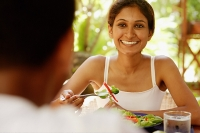 Couple eating, woman holding fork and smiling at man across from her - Asia Images Group
