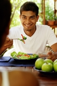 Man eating salad, looking at person opposite him - Asia Images Group