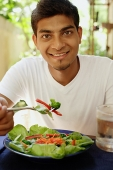 Man eating salad, looking at camera - Asia Images Group