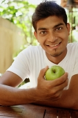 Man holding apple, looking at camera - Asia Images Group