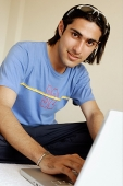 Man in front of laptop, looking at camera - Asia Images Group