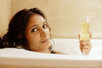Woman in bathtub, holding champagne glass - Asia Images Group