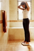 Woman in bathroom, standing on weight scale, looking down - Asia Images Group