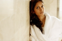 Woman in bathrobe, leaning on wall, looking at camera - Asia Images Group