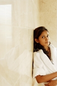 Woman in bathrobe, leaning on wall, looking at camera, portrait - Asia Images Group